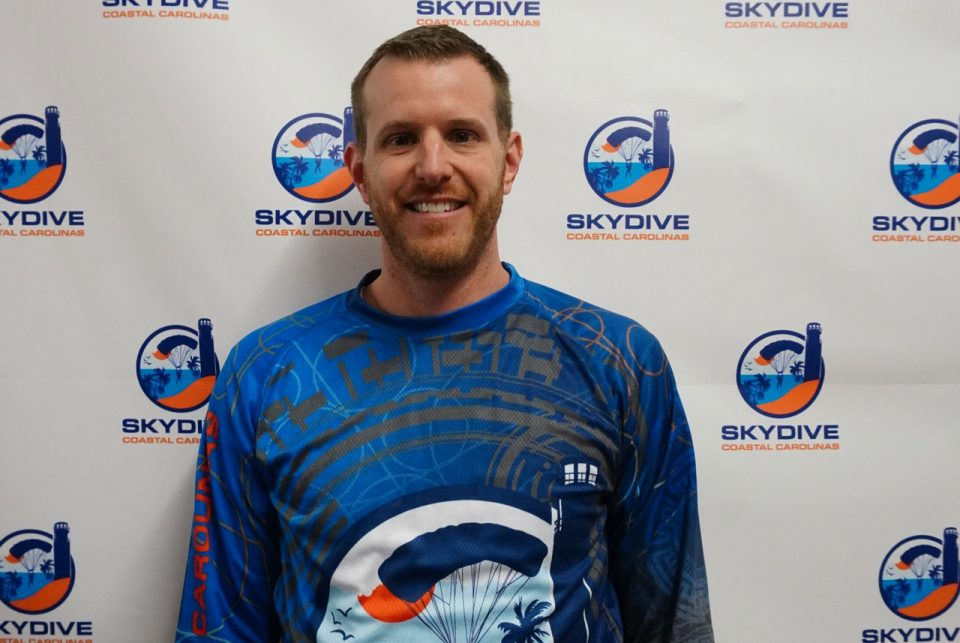 Headshot of Skydive Coastal Carolinas skydiving instructor and co-owner Blake Strong in front of backdrop with Skydive Coastal Carolinas logo