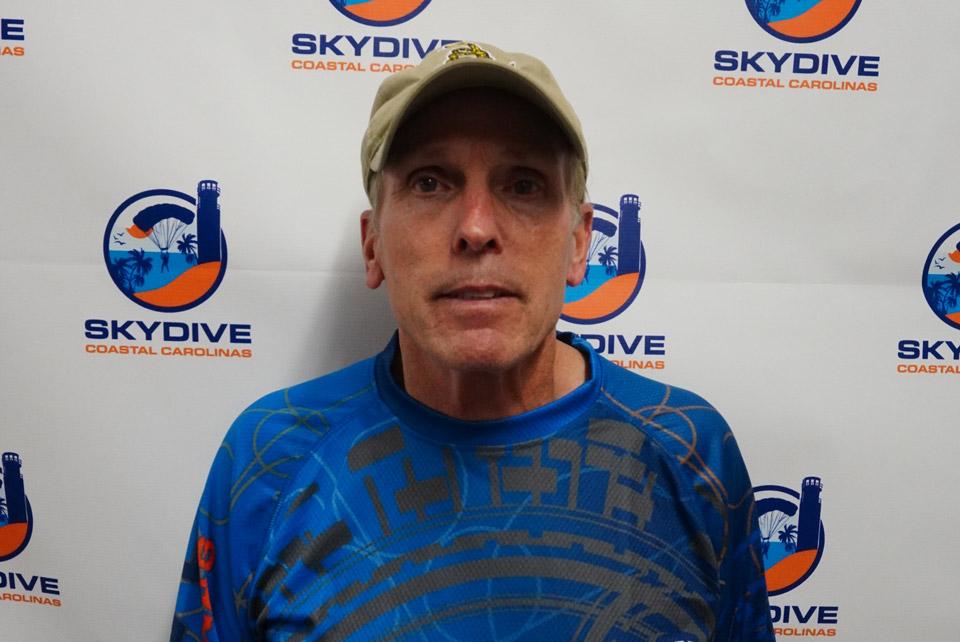 Headshot of of Skydive Coastal Carolinas skydiving instructor Robert Mehl in front of backdrop with Skydive Coastal Carolina Logo