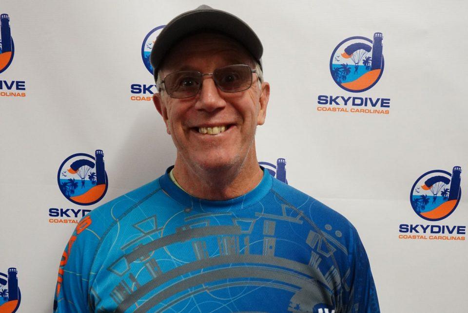 Headshot of Skydive Coastal Carolinas owner Brian Strong in front of backdrop with Skydive Coastal Carolinas logo