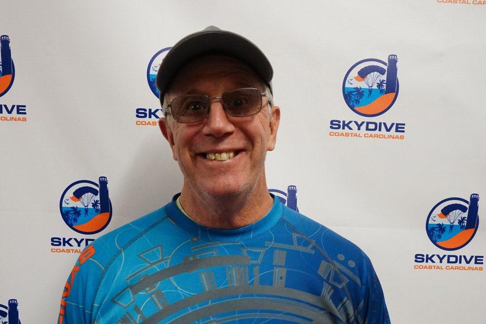 Headshot of of Skydive Coastal Carolinas owner Brian Strong in front of backdrop with Skydive Coastal Carolinas logo