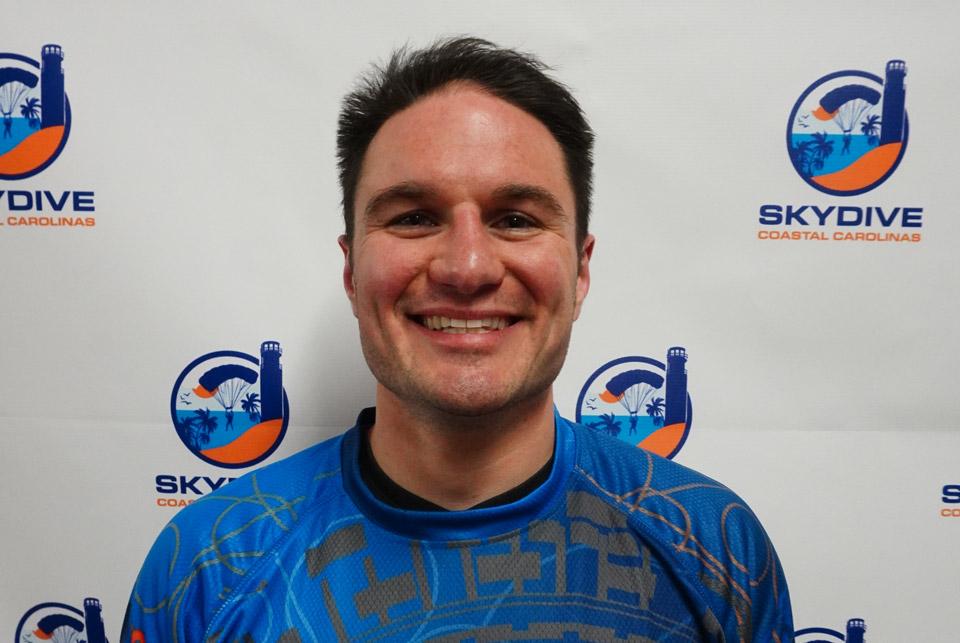 Headshot of of Skydive Coastal Carolinas skydiving instructor Christopher Dunbar in front of backdrop with Skydive Coastal Carolina Logo