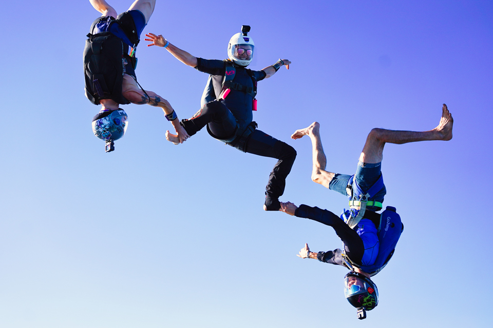 Smiling female skydiver in white helmet holds a sit position while two head down freeflyers each grip one of her feet