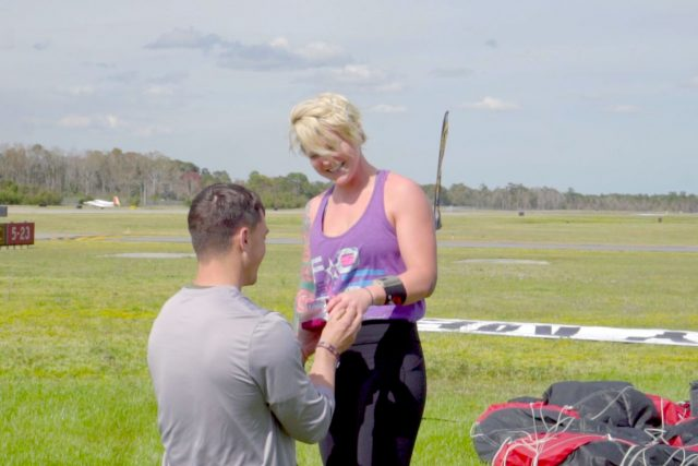Young man kneels before smiling young woman to slip on engagement ring after NC skydiving proposal