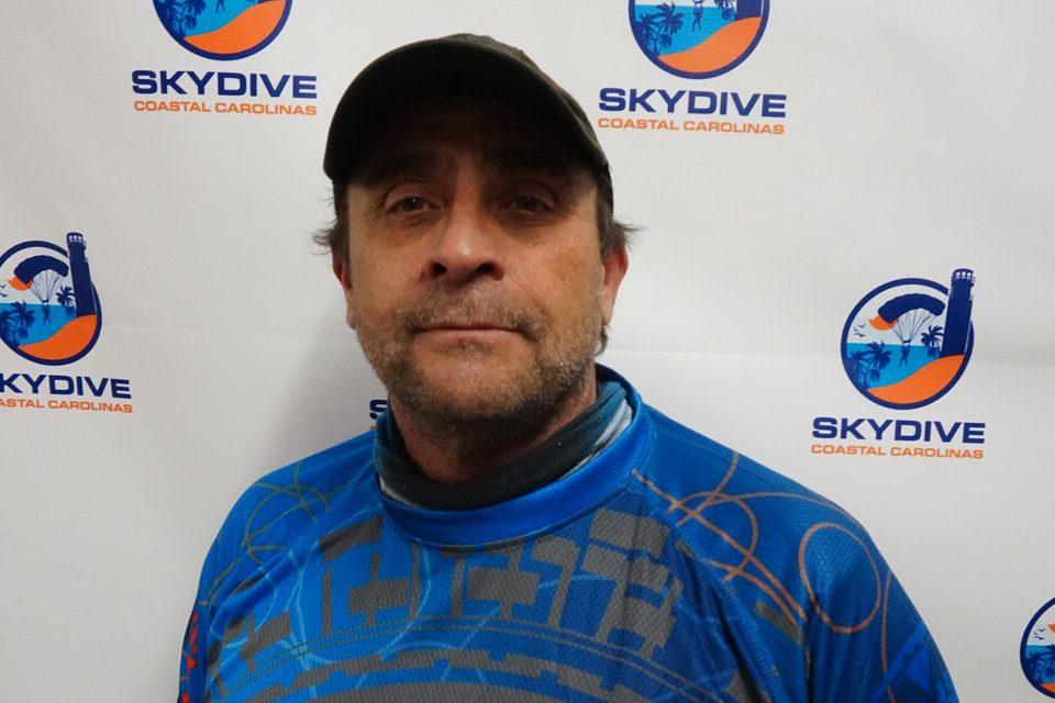 Headshot of of Skydive Coastal Carolinas skydiving instructor Michael Daniel in front of backdrop with Skydive Coastal Carolina Logo