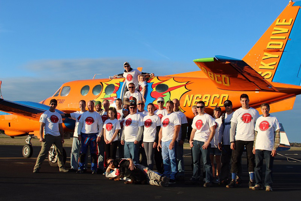 Group of skydivers posting in front of Beechcraft King Air with custom pop art paint job