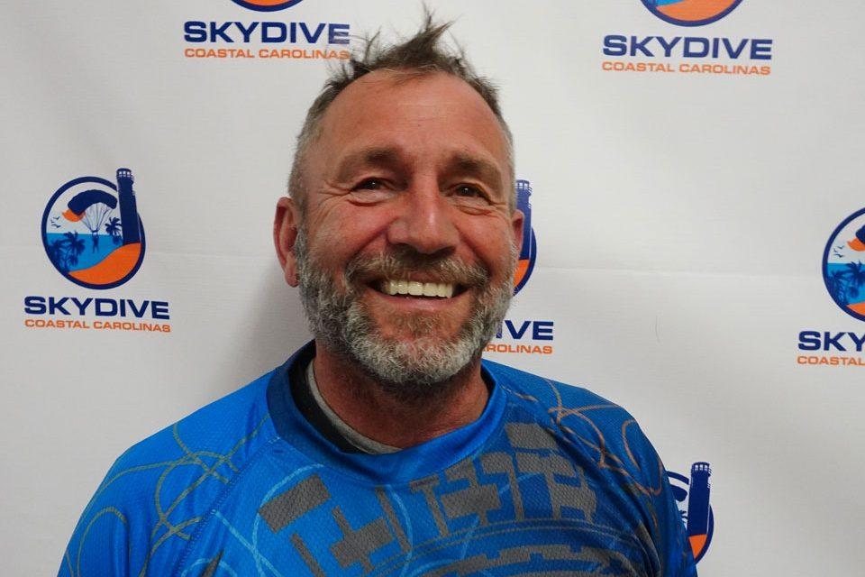 Headshot of Skydive Coastal Carolinas skydiving instructor Thomas Herzog in front of backdrop with Skydive Coastal Carolinas Logo