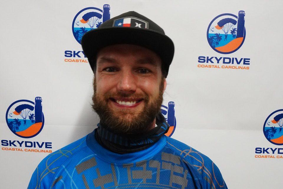 Headshot of of Skydive Coastal Carolinas skydiving instructor Tyler Clark in front of backdrop with Skydive Coastal Carolinas logo