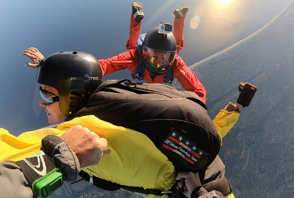 Accelerated Freefall instructor in a red relative work suit on main side looking over accelerated freefall student in a yellow jumpsuit to the reserve side instructor
