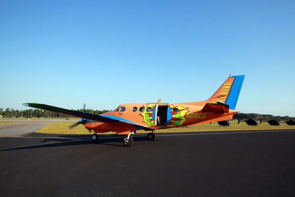Beechcraft King Air B90 with vibrant orange paint job on runway with a row of black helicopters in the background