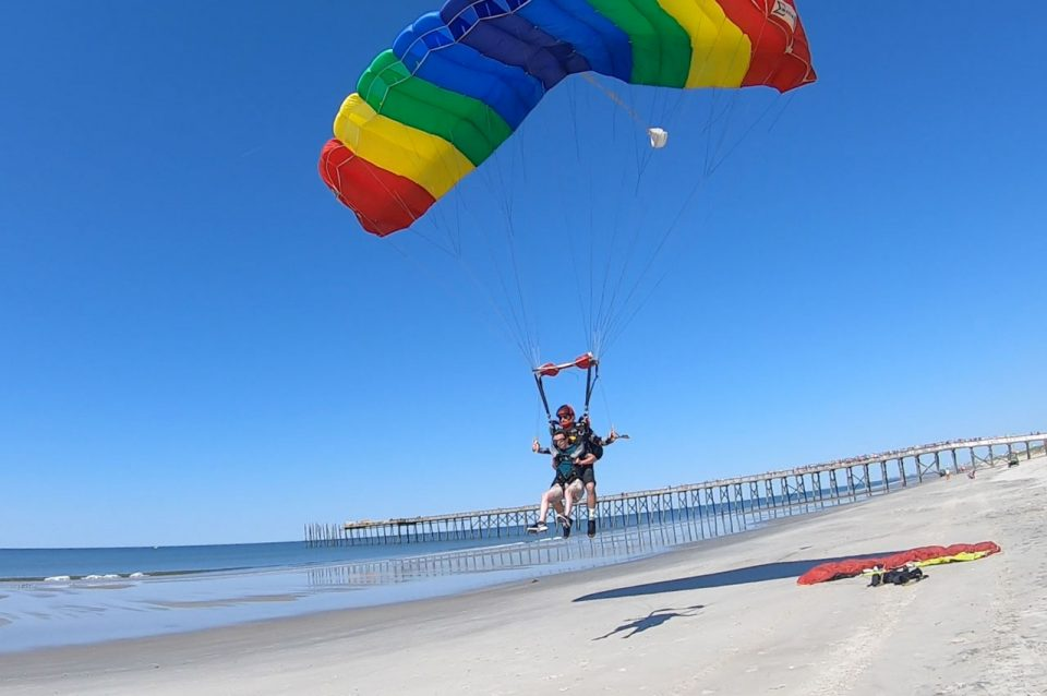 Tandem skydiving pair beneath a rainbow colored parachute landing on the beach