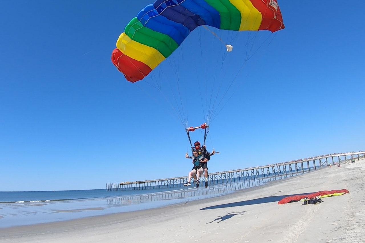 Tandem skydiving pair beneath a rainbow colored parachute landing on the beach