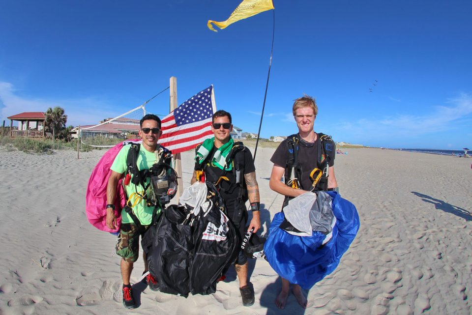 Three skydivers with parachutes in hand stand in front of American flag and volleyball net after skydiving on the beach