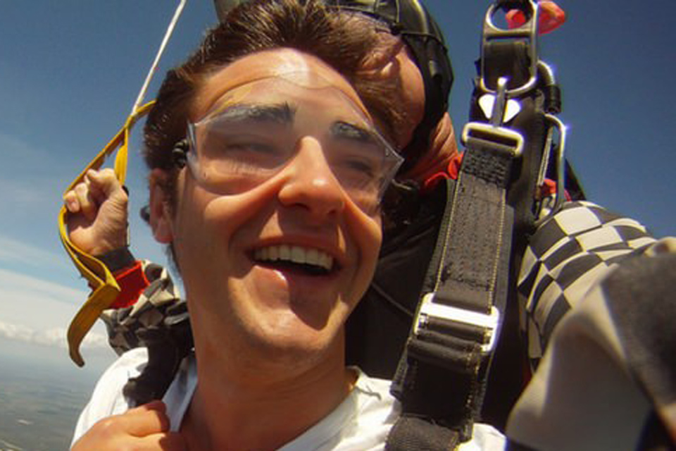 Elated tandem skydiving student enjoys the ride beneath the parachute