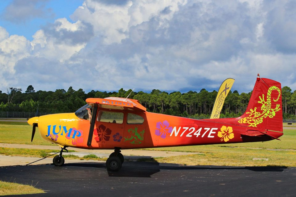 Tropically painted orange Cessna- 182 with multicolored hibiscus flowers, bright green frog, and a tribal gecko design on the tail