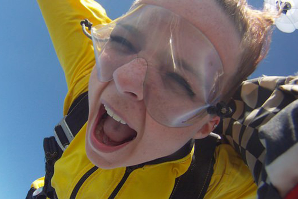 Freckled female tandem skydiving student yelling in freefall