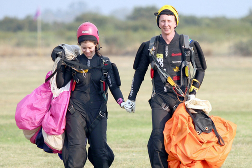 Female skydiver in pink helmet and male skydiver in yellow helmet holding hands as they walk in from the landing area