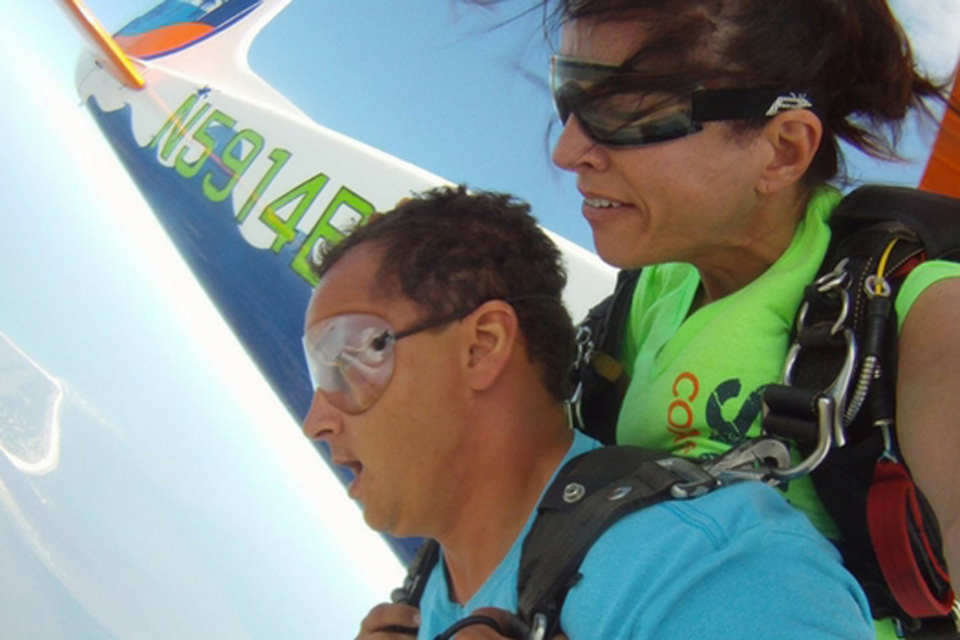 Tandem skydiving student with unsure expression and female tandem skydiving instructor as they exit the Cessna-182
