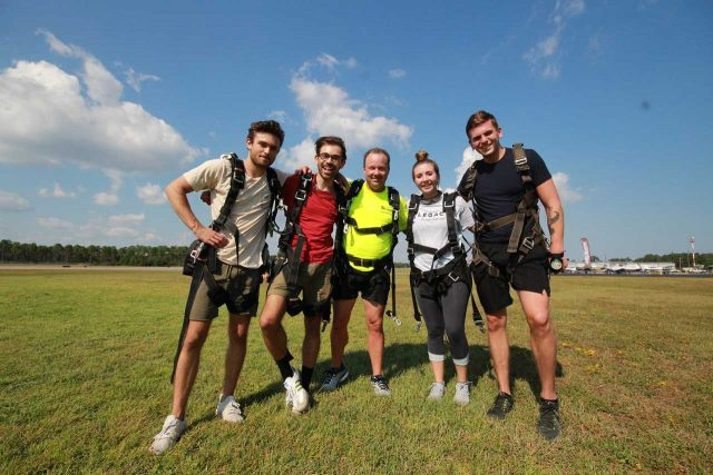 Five tandem skydiving students pose for a picture in the landing area wearing skydiving harnesses after landing