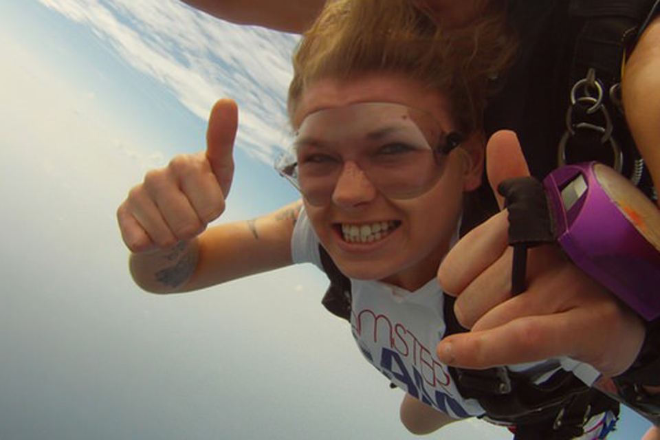 Female tandem skydiving student in clear goggles with purple analog altimeter on her hand gives thumbs up