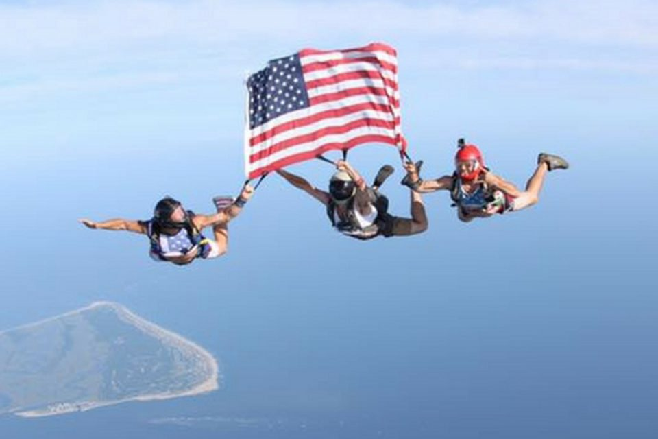 Three licensed skydivers holding the American flag in freefall over the ocean