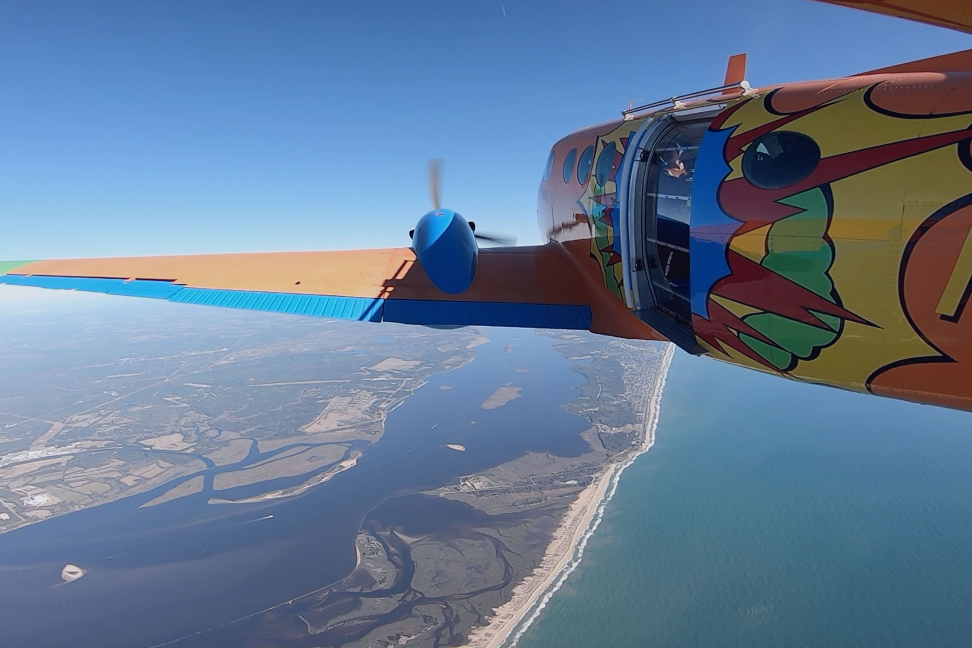 Beechcraft King Air with vibrant orange, blue, red, yellow and green pop art paint job flying over the coast of Oak Island