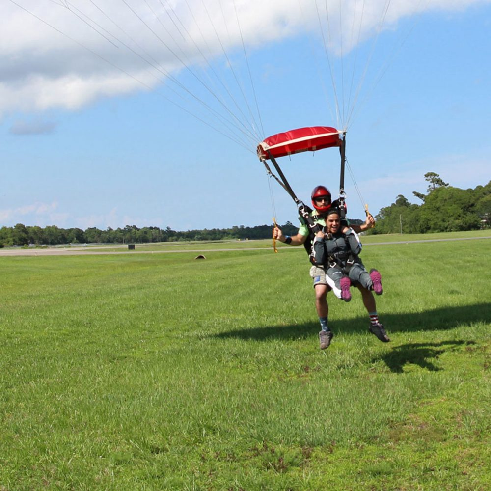 Tandem instructor and excited student land the parachute gently on bright green grass in Oak Island, NC