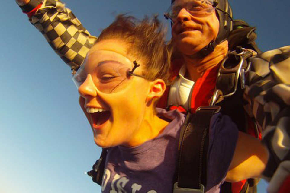 Close up of tandem skydiving student enjoying freefall with a smiling tandem instructor behind her