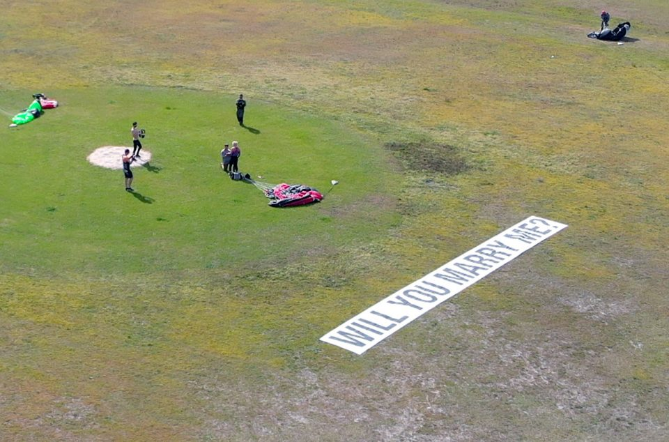 "Three skydivers in the landing area record as man on bended knee proposes. There is a sign that says ""will you marry me?"" in the foreground. A fourth skydiver in the top right corner collects his parachute from the ground."