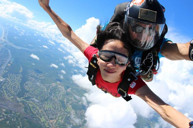 Tandem skydiving student with a peaceful expression and partially closed eyes stretches out arms as if in flight