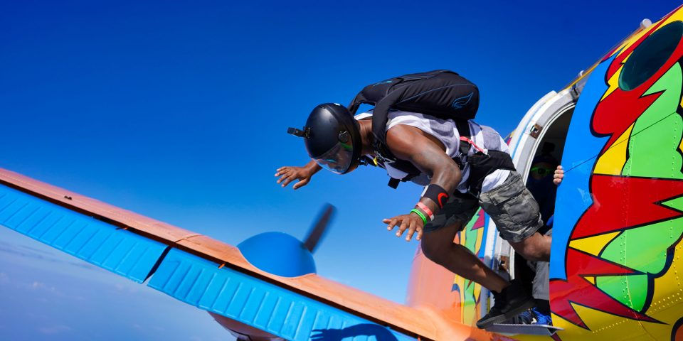 Athletic male skydiver with black helmet exiting Beechcraft King Air with bright orange, blue, red, yellow and green paint job