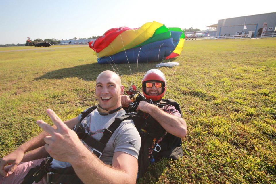 Bald tandem student giving a peace sign as smiling skydiving instructor in red helmet disconnects the harness after Myrtle Beach skydiving