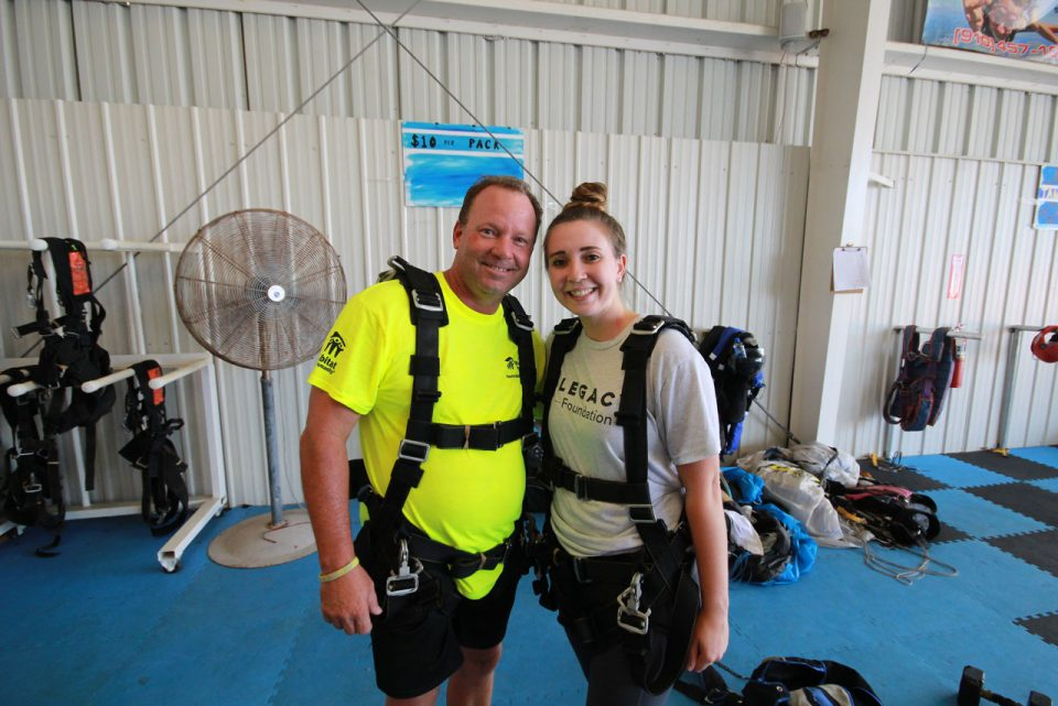 Two first time tandem skydiving students in harnesses smiling for a photo before preparing to skydive near Myrtle Beach
