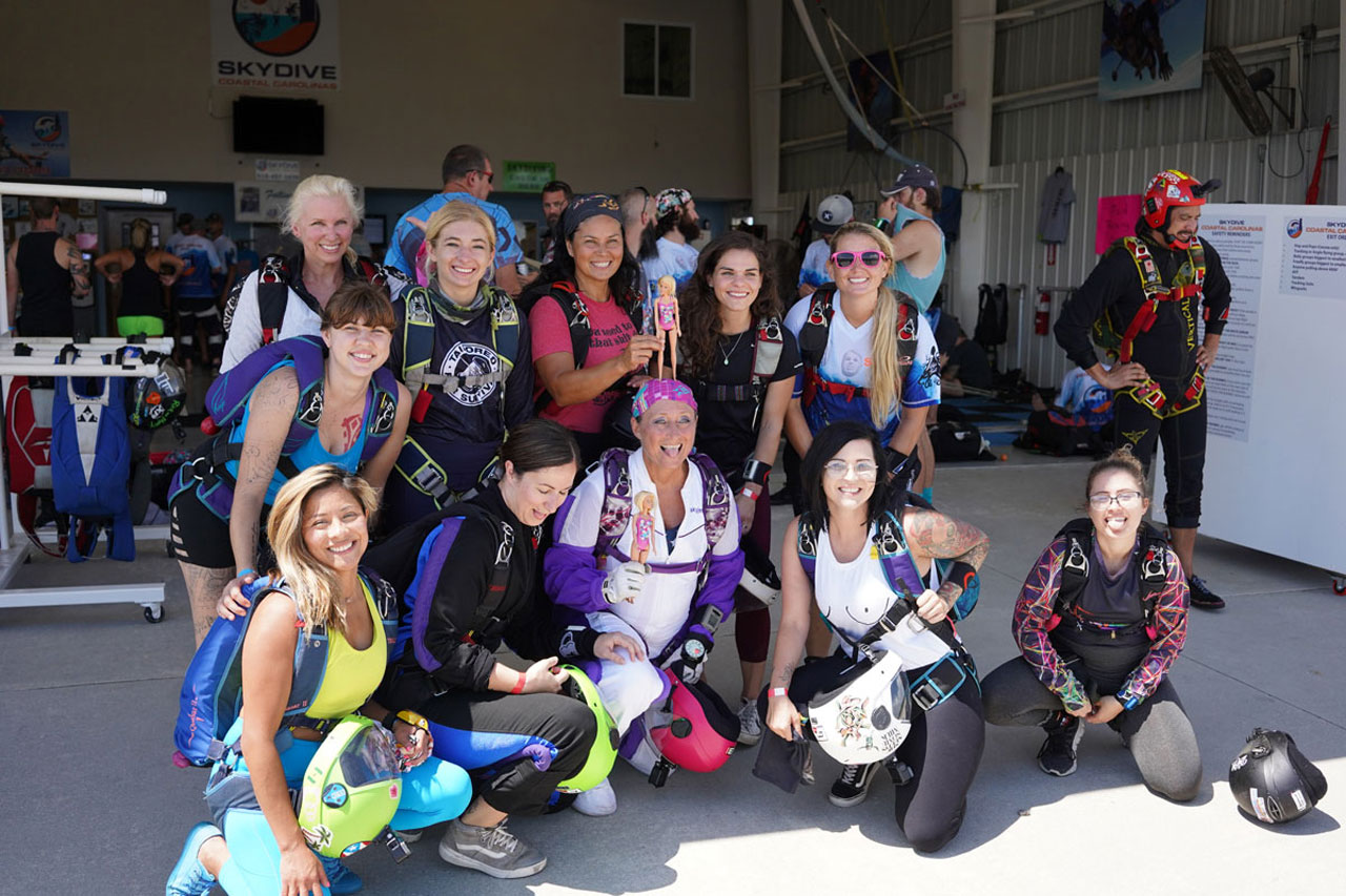Eleven female skydivers posing with smiles and tongues out. The center two female skydivers are holding barbies.