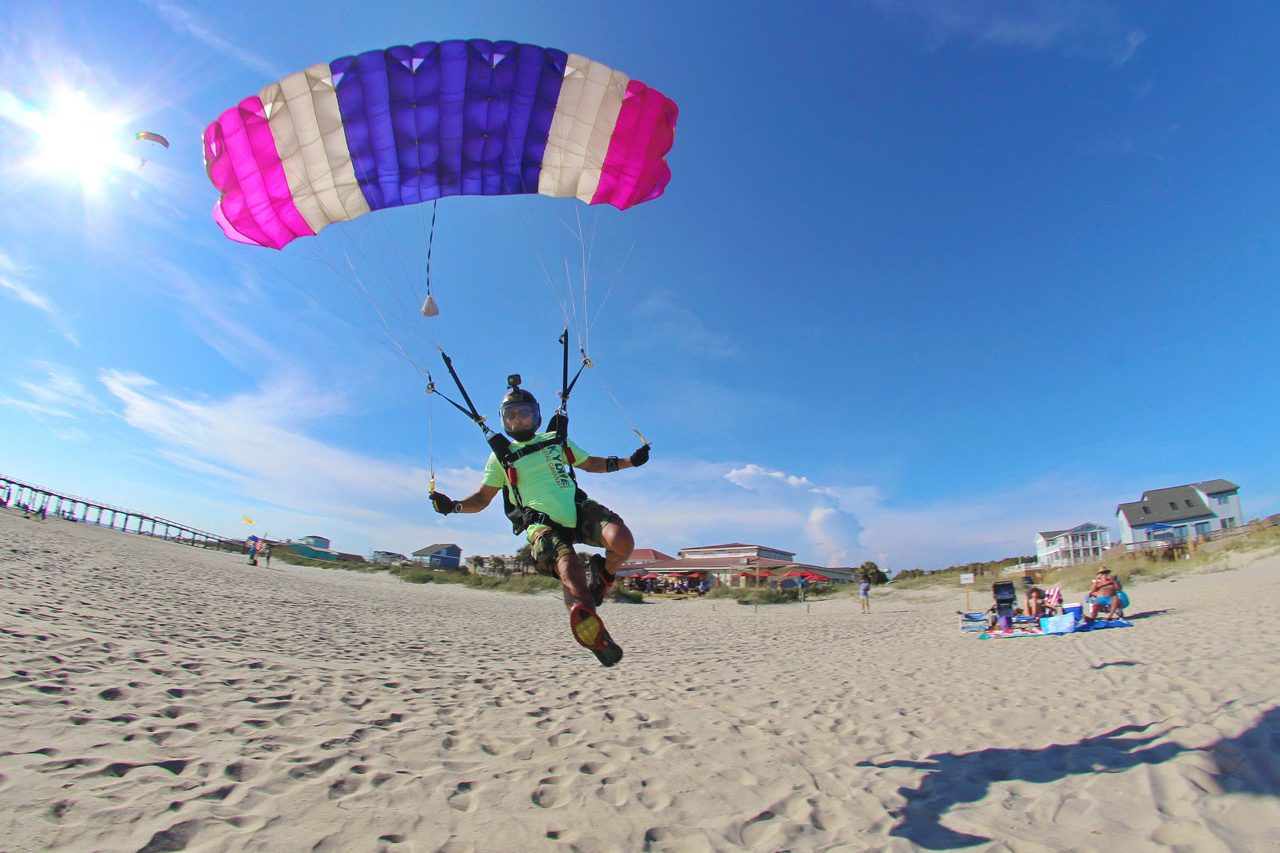 Licensed skydiver coming in for landing on the beach beneath a pink, white, and purple striped parachute