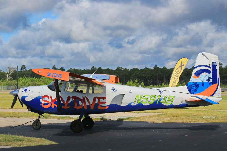 Side view of custom painted Cessna 182 aircraft with blue waives, a shark fin, and the Skydive Coastal Carolinas logo painted on the tail