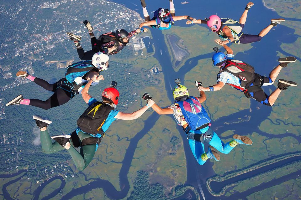 Seven licensed skydivers hold hands to build a round formation in freefall over the intracoastal waterway