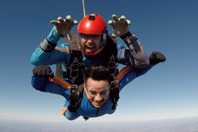 Tandem skydiving instructor in red helmet with hands raised like claws jumping with tandem skydiving student in blue and orange jumpsuit near Myrtle Beach