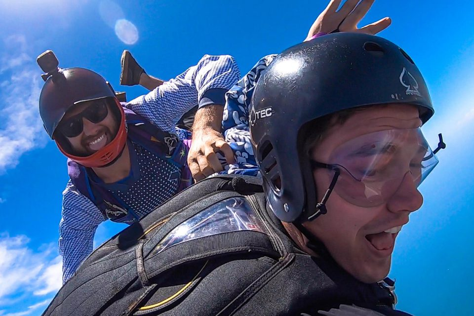 Accelerated freefall student in protec helmet and skydiving instructor with open visor sticking his tongue out