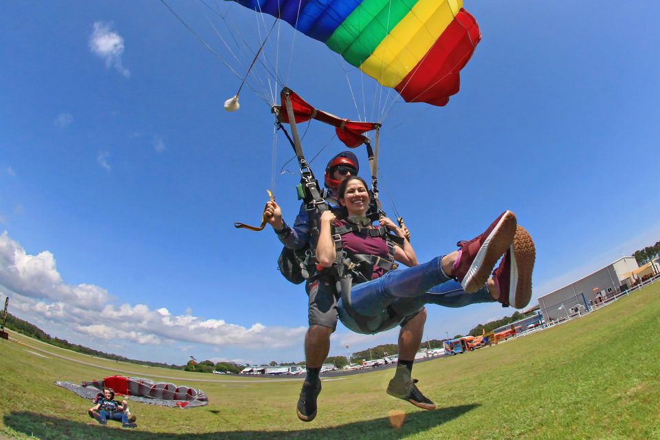 Female tandem skydiving student lifting legs as tandem instructor touches down