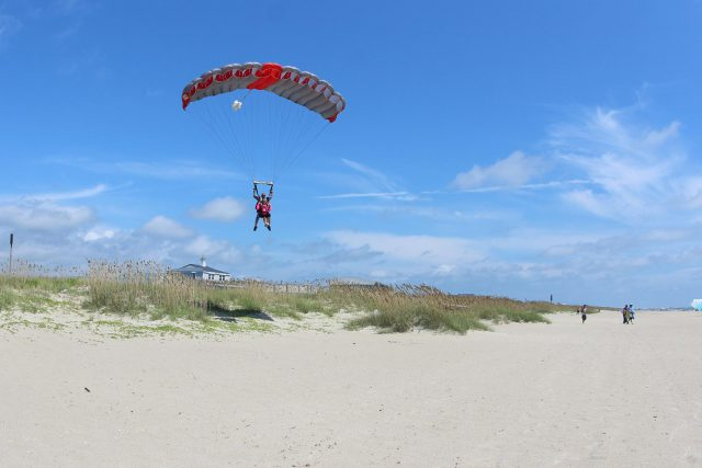 Tandem skydiving instructor and student landing on the beach beneath a gray and red parachute