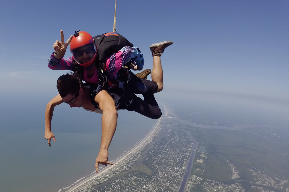 Tandem student pointing at ground while tandem skydiving instructor gives a peace sign during freefall over Oak Island, NC