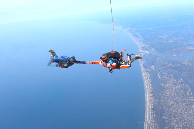Skydiving videographer takes the hand of a tandem skydiving student over the coast of Oak Island, NC