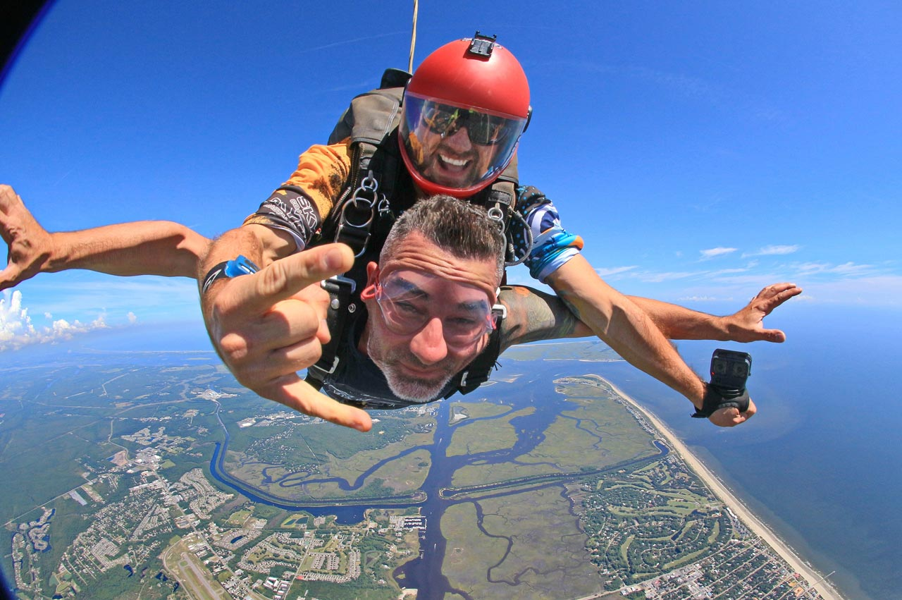 Tandem skydiving instructor with a go pro attached on one hand gives the rock on symbol with his other hand while attached to a tandem skydiving student in freefall over the coast of Oak Island, NC