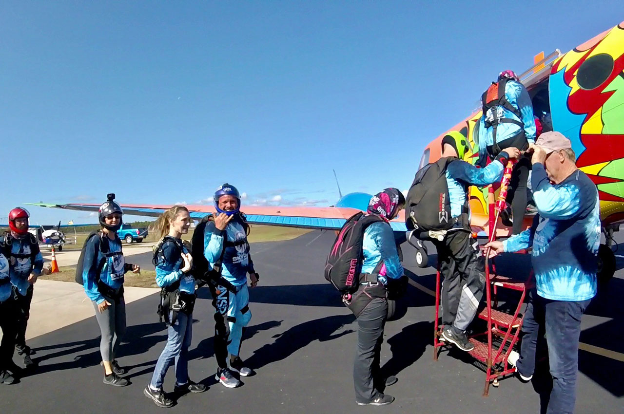 Excited tandem skydivers and licensed skydivers board brightly painted Beechcraft King Air B90