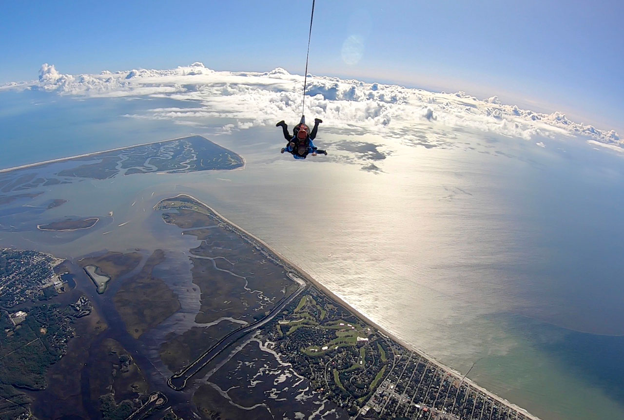 tandem instructor and tandem student in freefall with a stunning ocean backdrop and views of Wilmington, NC
