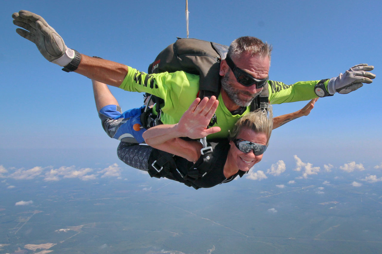 Tandem skydiving instructor in dark goggles and student in mirrored goggles smile in freefall