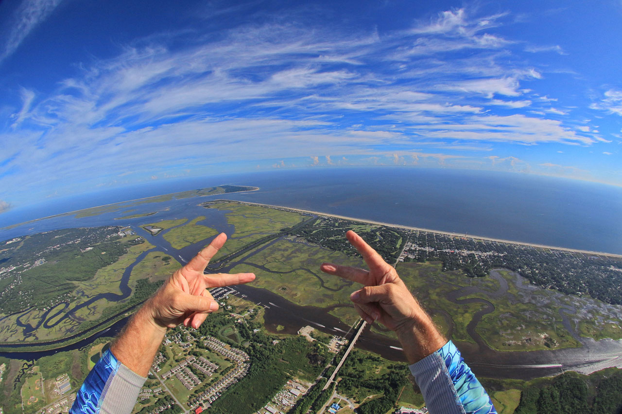 First person view of hands giving peace signs over coast of Wilmington, NC