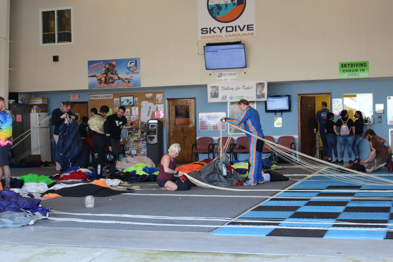 Skydivers pack parachutes on packing mat of hangar while tandem skydiving customers check in at the manifest window