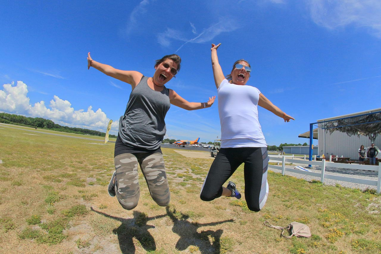 A smiling female tandem skydiver in gray tank top and camo pring yoga pants and an excited female tandem student in a white shirt and black and gray yoga pants both jump for joy in front of a bright blue sky
