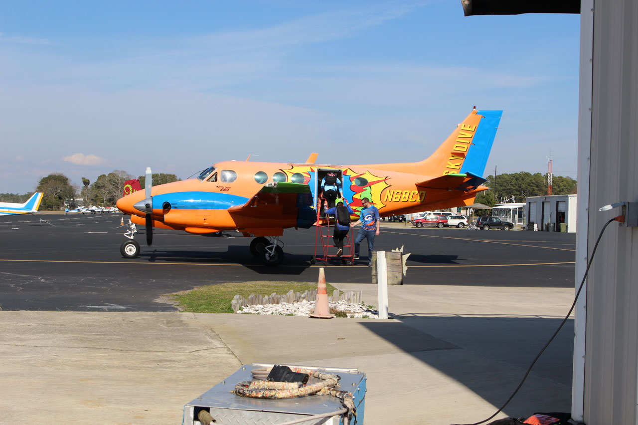 Beechcraft King Air B90 tail number N68CD with vibrant orange and blue custom paint job
